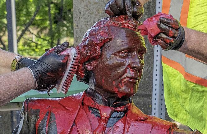 Workers remove red paint from a Sir John A. Macdonald statue in Charlottetown on Friday June 19, 2020. THE CANADIAN PRESS/John Morris
