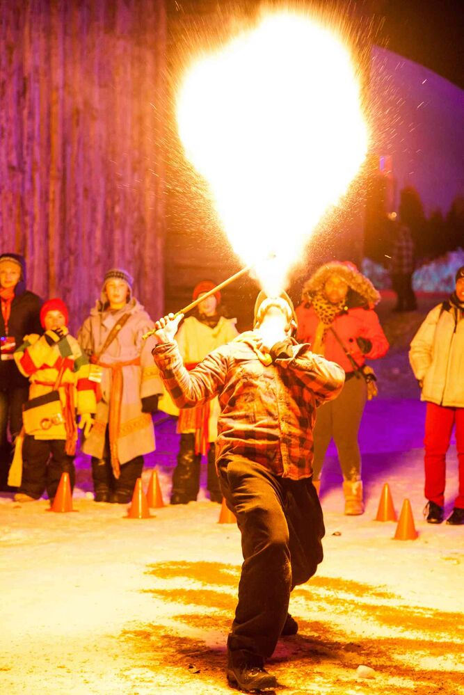 Isaac Girardin breathes fire as Festival goers look on during the opening night of the Festival du Voyageur.  