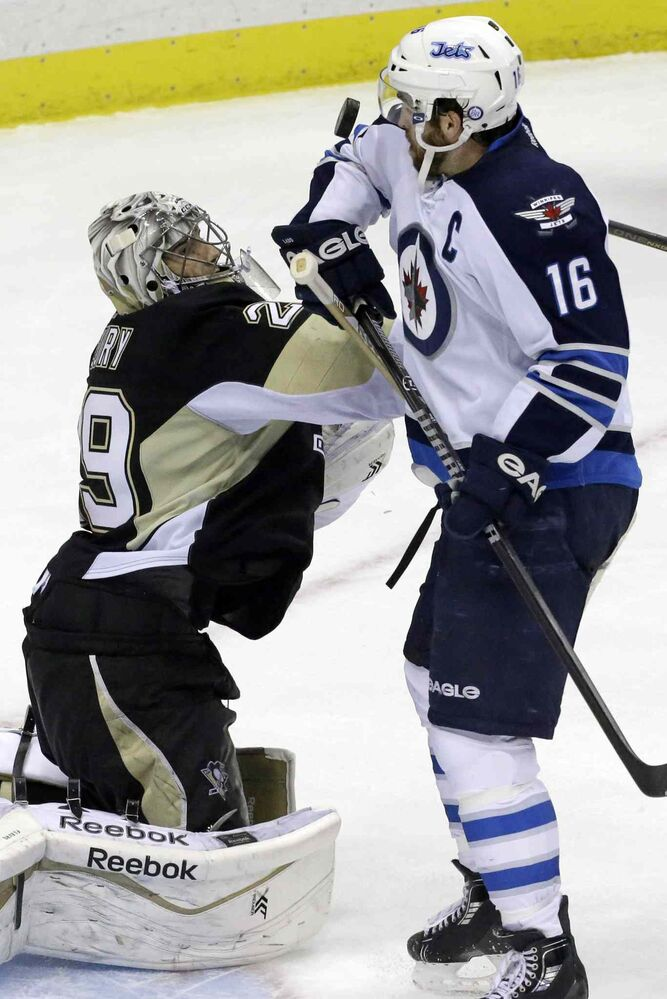 Penguins goalie Marc-Andre Fleury keeps his eye on a rebound in front of Jets captain Andrew Ladd during the third period. (GENE J. PUSKAR / THE ASSOCIATED PRESS)