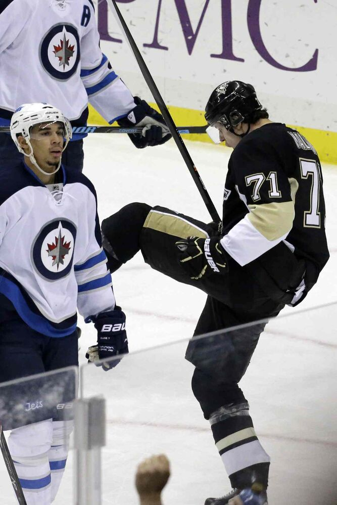 Penguins forward Evgeni Malkin celebrates a goal as Jets forward Evander Kane skates back to his bench in the third period.