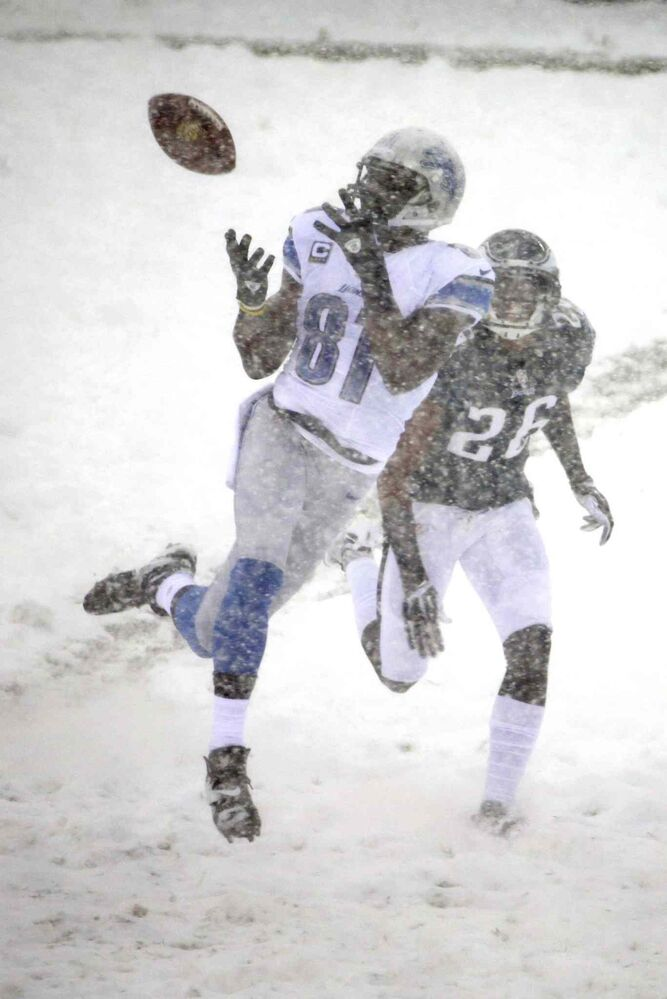 Detroit Lions' Calvin Johnson (left) catches a pass as Cary Williams of the Philadelphia Eagles gives chase during the first half. (Matt Rourke / The Associated Press)