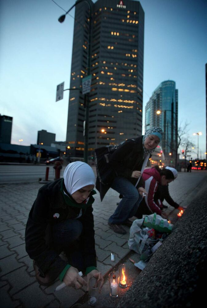 Syrian Winnipeggers struggle to light candles along Main Street near Pioneer Avenue Thursday evening. A small vigil with about 30 participants marked the 1st anniversary of the Syrian uprising.  March 15, 2012  (Phil Hossack / Winnipeg Free Press)