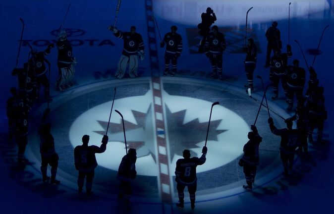 Winnipeg Jets players raise their sticks as they are introduced to the crowd prior to their inaugural game against the Montreal Canadiens at the MTS Centre in Winnipeg, Sunday, Oct. 9, 2011. THE CANADIAN PRESS/Jonathan Hayward</p>