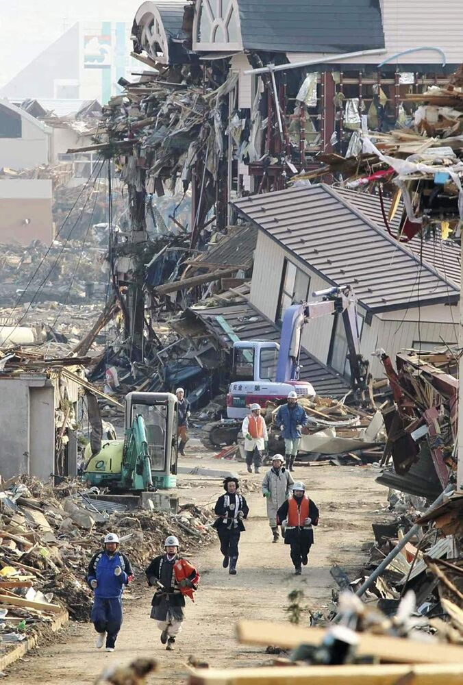 Rescue workers run through rubble to the higher place in Rikuzentakata in Iwate Prefecture, northeastern Japan, upon hearing a tsunami warning Sunday, March 13, 2011, two days after a powerful earthquake-triggered tsunami hit the country's east coast. (AP Photo/The Yomiuri Shimbun, Osamu Kanazawa)