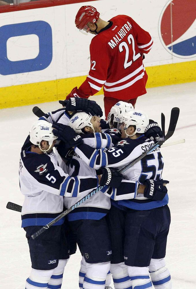 Winnipeg Jets' Chris Thorburn (22), centre, celebrates his game-winning goal with teammates Mark Stuart (5) and Mark Scheifele (55) during the third period of Tuesday's game against the Carolina Hurricanes. The Jets beat the Canes 2-1. (Chris Seward / Raleigh News & Observer/ Tribune Media MCT)