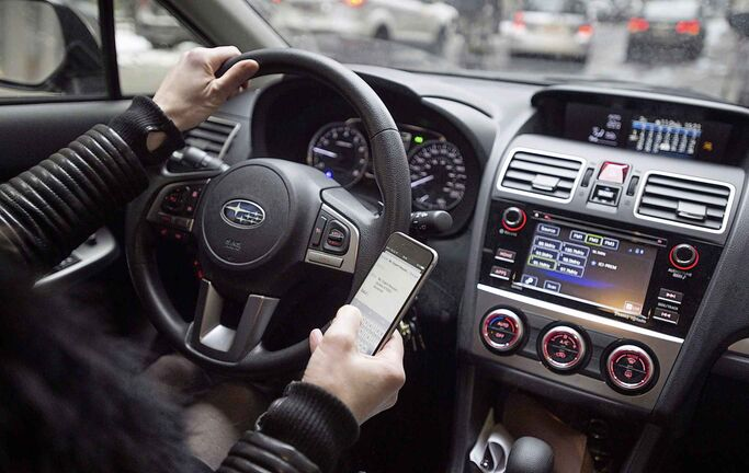 A driver texts while at the wheel in this photo illustration in Montreal on January 25, 2017. Manitoba drivers who use a hand-held cell phone behind the wheel will face stiffer penalties as of Nov. 1.The fines will jump to $672 from $203, and the number of demerit points will increase to five points from two. THE CANADIAN PRESS/Paul Chiasson