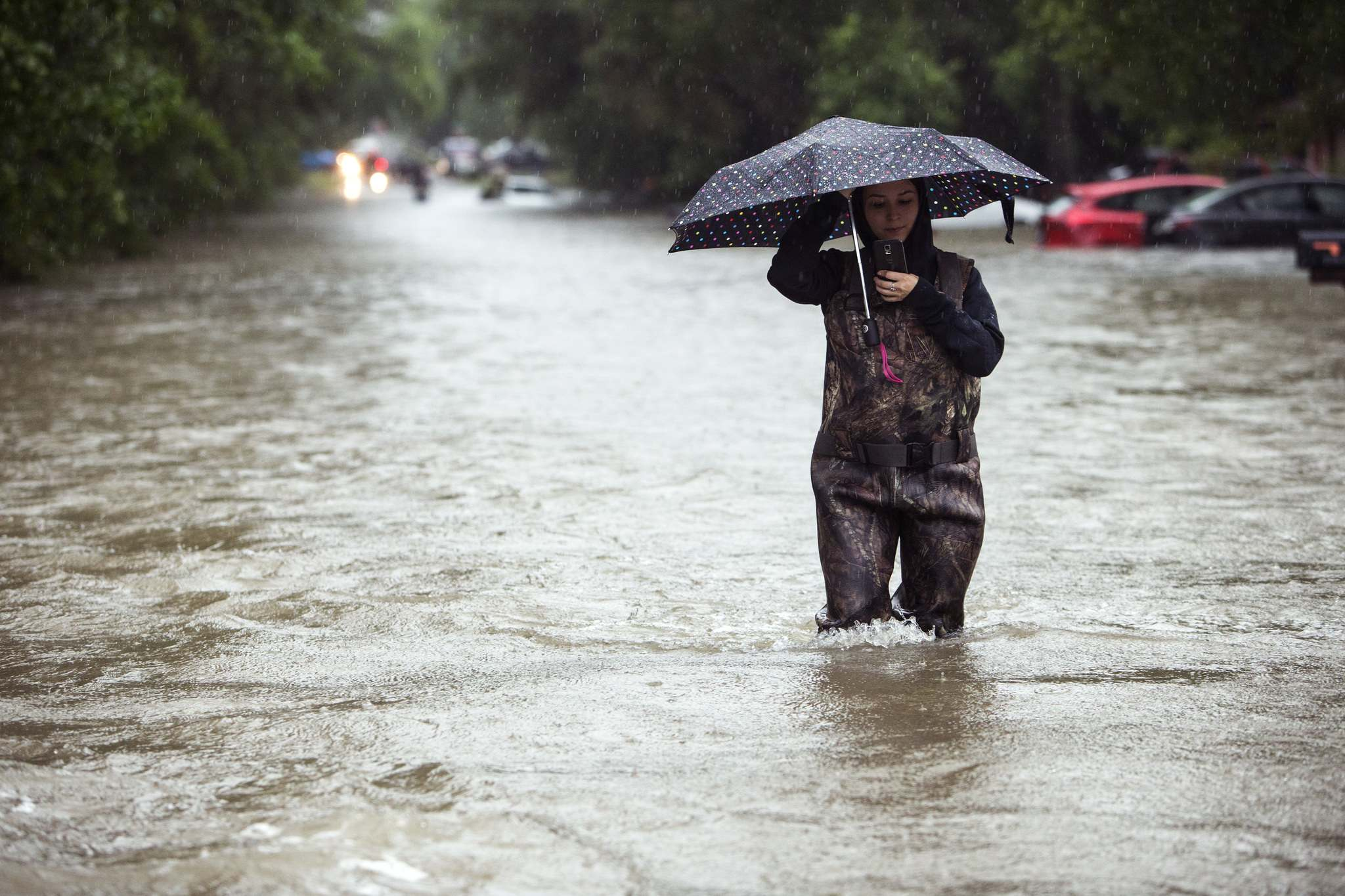 Brett Coomer/Houston Chronicle via AP</p><p>A woman walks out of high water in the Timber Lakes Timber Ridge subdivision on Monday, April 18, 2016, in The Woodlands, Texas. More than a foot of rain fell Monday in parts of Houston, submerging scores of subdivisions and several major interstate highways, forcing the closure of schools and knocking out power to thousands of residents who were urged to shelter in place.</p>