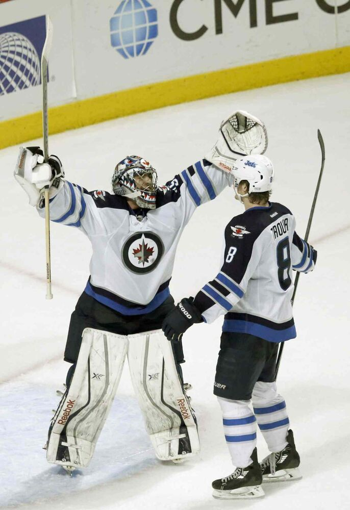 Jets goalie Al Montoya celebrates the Jets' 3-1 win over the Blackhawks with Jacob Trouba. (Charles Rex Arbogast / The Associated Press)