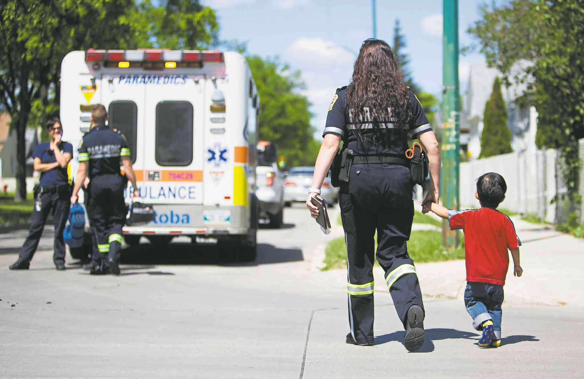 A paramedic leads a boy to safety after five children and their child-care provider escaped a fire in a home daycare on Burrows Avenue Thursday morning.