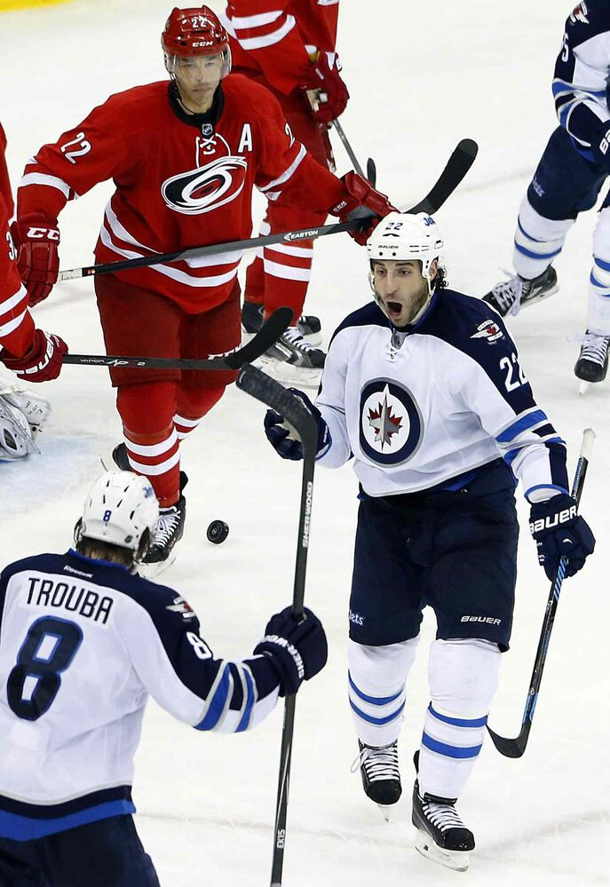 Winnipeg Jets' Chris Thorburn (22) celebrates his go-ahead goal with teammate Jacob Trouba (8) as Carolina Hurricanes' Manny Malhotra (22) looks on during the third period of Tuesday's game.