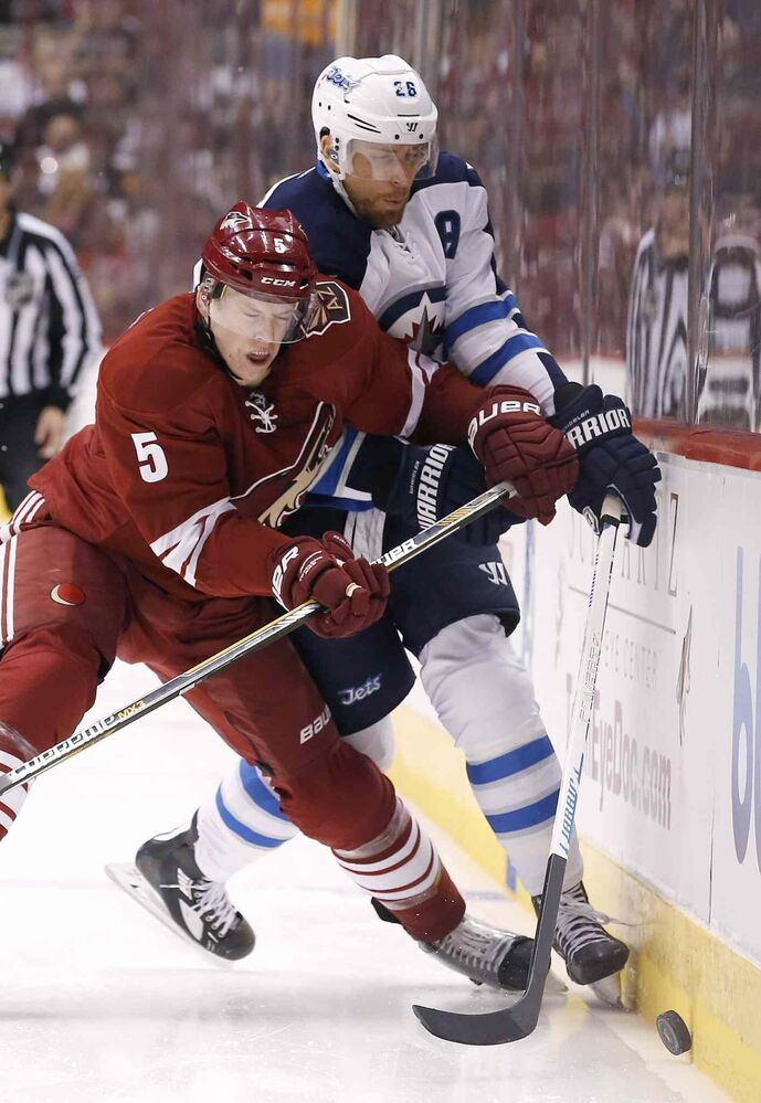 Arizona Coyotes' Connor Murphy (5) checks Winnipeg Jets' Blake Wheeler (26) into the boards during the first period of an NHL hockey game Thursday, Oct. 9, 2014, in Glendale, Ariz. (Ross D. Franklin / The Associated Press)