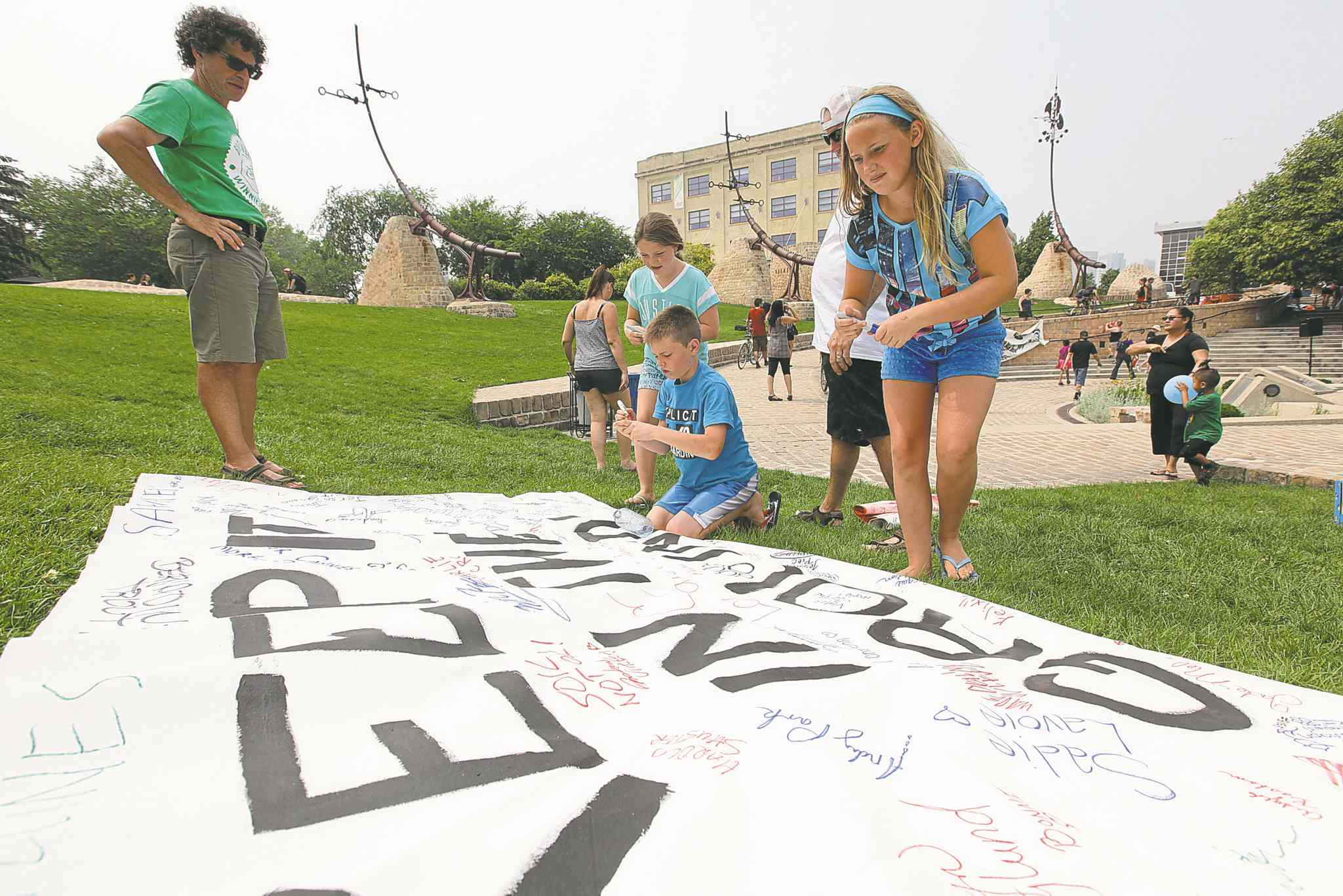 Children sign a banner stating 'Keep it in the ground,' in the Oodena Circle at The Forks Saturday, part of events held across the country urging a halting of oilsands expansion.