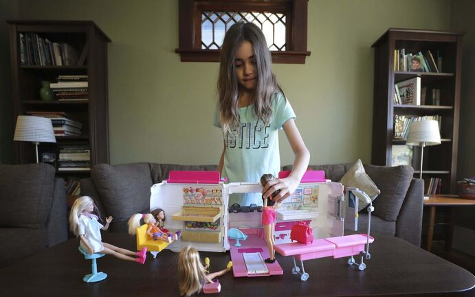 Anna Milne-Karn plays with her pink Barbie mobile clinic toy after school.