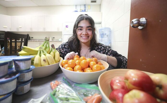 Tihiya Maheen, a Grade 10 student at Glenlawn Collegiate, gives out fruit, yogurt and other healthy snacks to fellow students.