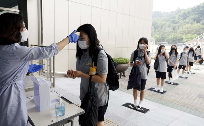 Students wearing face masks to help protect against the spread of the coronavirus stand in a line to have their body temperatures checked before entering their classrooms at a middle school in Chungju, South Korea last month. (In Jin-hyun / Newsis files)