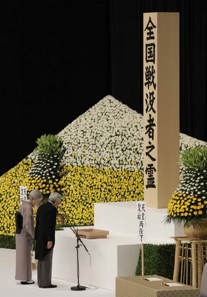 Japan's Emperor Akihito, right, and Empress Michiko bow before the main altar decorated with huge bank of chrysanthemums as they offer prayers for the war dead during a memorial service at Budokan Martial Arts Hall in Tokyo, marking the 67th anniversary of its World War II surrender. (AP Photo/Shizuo Kambayashi)