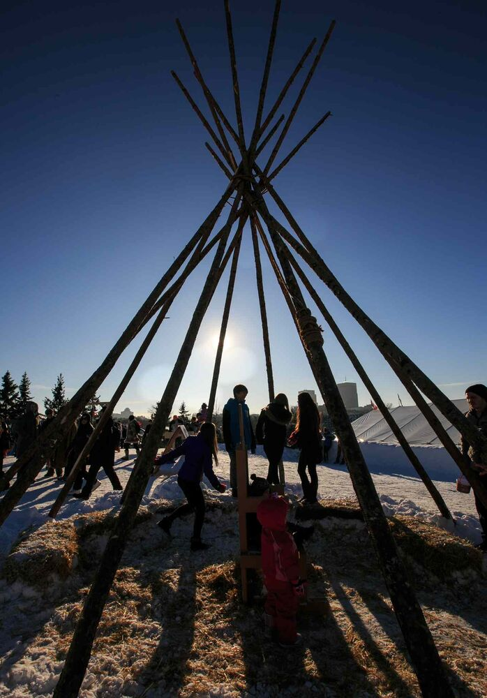 Teens in a teepee in the snow park at Festival du Voyageur on Louis Riel Day. 