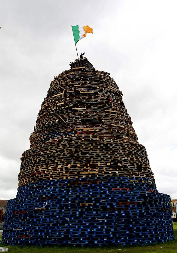A child stands on a massive bonfire in the Shankill Estate in West Belfast, Northern Ireland. Thousands of bonfires have been built in Protestant areas across Northern Ireland for the annual July 11 bonfire night where they celebrate the 1690 battle of the Boyne were the Protestant King William of Orange defeated the Catholic King James. (AP Photo/Peter Morrison)