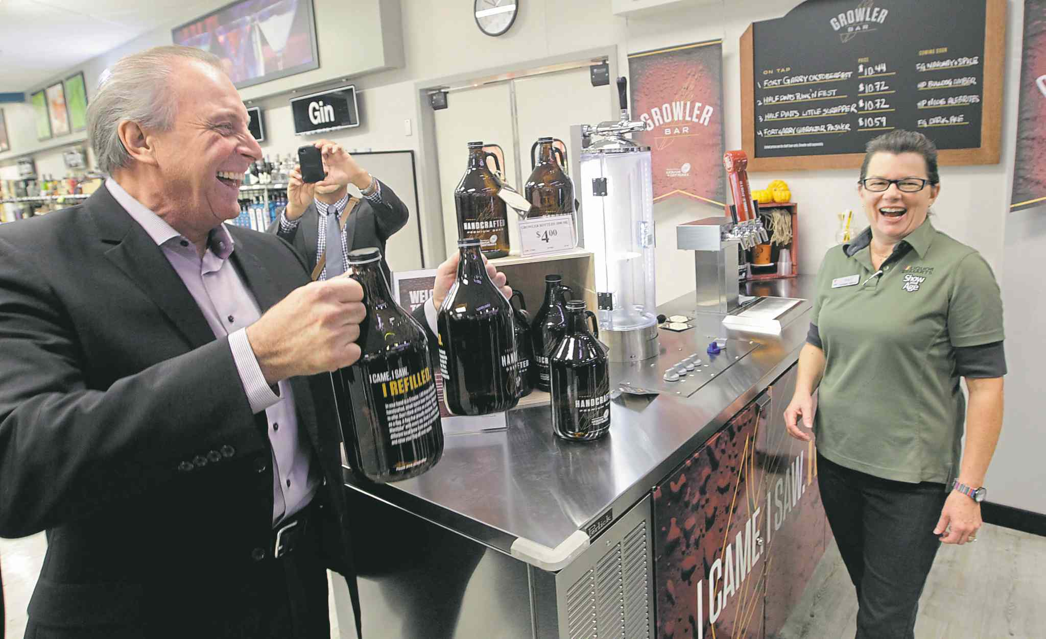 The MGEU says Manitobans are happy liquor sales are controlled by the provincial government. Above, Ron Lemieux, minister responsible for Liquor and Lotteries, yuks it up with Liquor Mart employee Tracy Jones at last year's launch of in-store Growler bars.