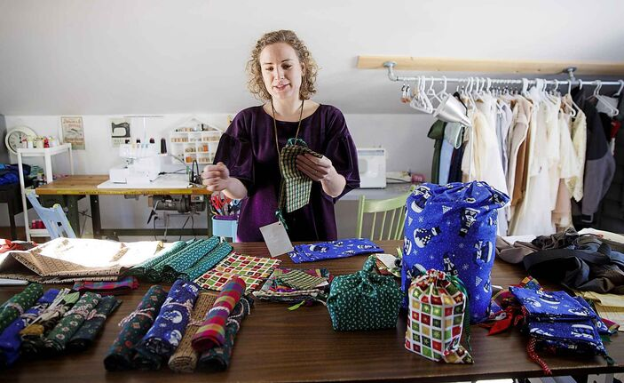MIKE DEAL / WINNIPEG FREE PRESS <p /> Anna-Marie Janzen chooses from among Christmas-themed fabrics for another guilt-free gift-wrapping alternative.