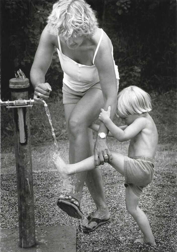 Nicholas Laporte, 4, gives his mother Mette a hand with a foot wash during the Winnipeg Folk Festival on Saturday afternoon, July 9, 1983. (STU PHILLIPS / WINNIPEG FREE PRESS)
