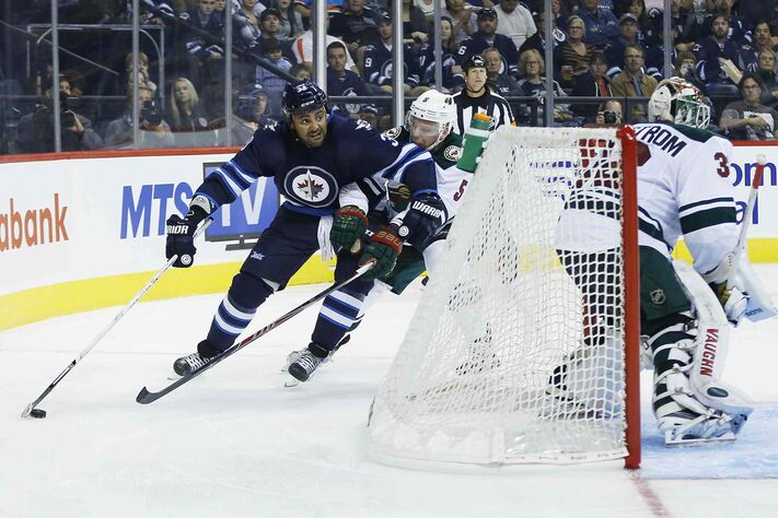The Winnipeg Jets' Dustin Byfuglien drives behind the net against the Minnesota Wild's Christian Folin in the second period Monday at the MTS Centre.