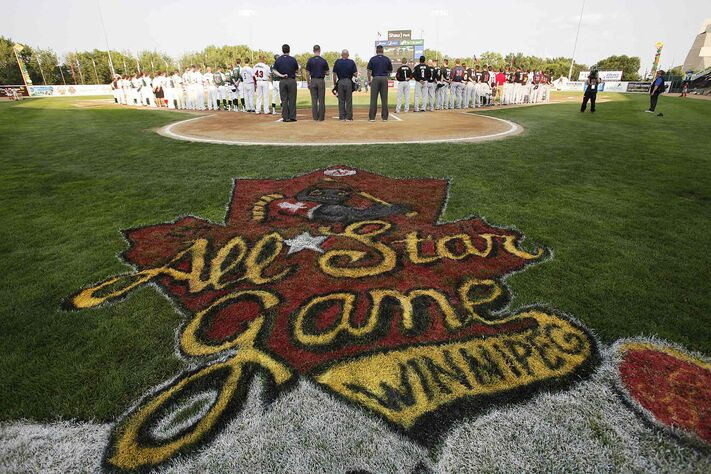 Teams line up for the singing of national anthems prior to the 2014 American Association All-Star game in Winnipeg Tuesday.