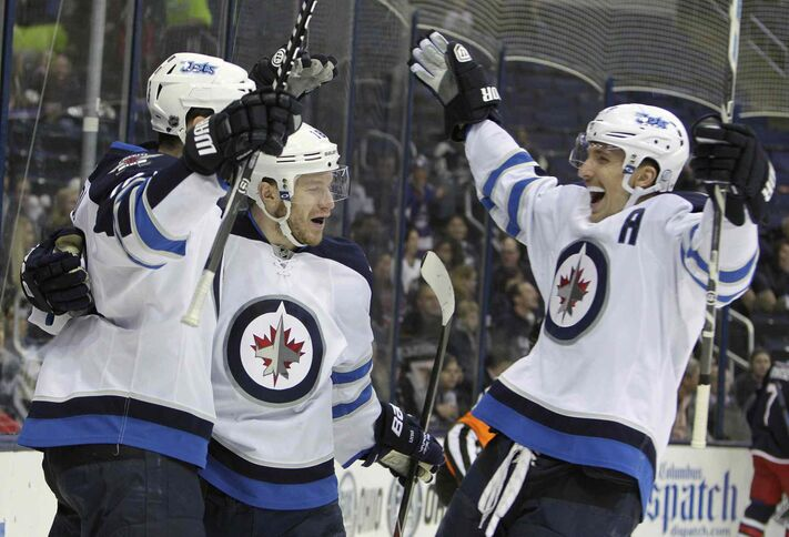 Winnipeg Jets' Bryan Little, centre, celebrates his first-period goal against the Columbus Blue Jackets with teammates Andrew Ladd, left, and Blake Wheeler. The Jets beat the Blue Jackets 4-2.