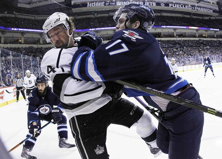 Winnipeg Jets forward Adam Lowry (17) checks Justin Williams of the Los Angeles Kings during second-period NHL action at the MTS Centre in Winnipeg Sunday.