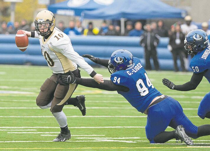 Manitoba Bisons quarterback Jordan Yantz breaks away from Montreal Carabins pursuers Emile Charron-Ligez (94) and Alex Cromer-Emond during the first half Saturday.
