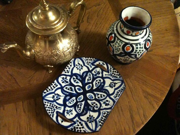 A tea pot, purchased in Essaouira, Morocco, and a ceramic vase and plate, purchased in Marrakech, Morocco.  The tea pot was haggled for, but the vase and plate were purchased in a fixed-price store.