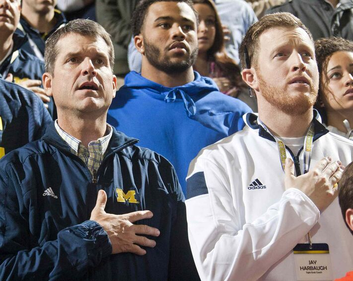 Michigan football head coach Jim Harbaugh, left, stands for the national anthem with son Jay, right, before an NCAA college basketball game against Northwestern at Crisler Center in Ann Arbor, Mich., in January.