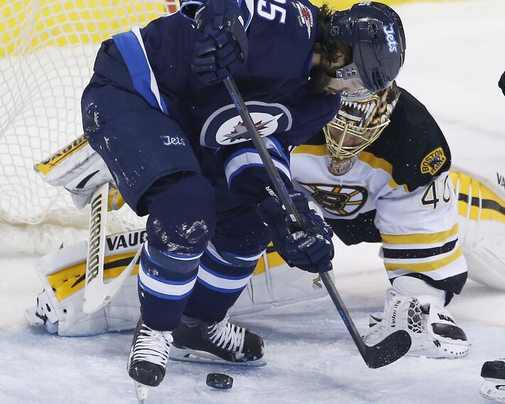 Winnipeg Jets' Mathieu Perreault (85) attempts the backhander against Boston Bruins goaltender Tuukka Rask (40) during first period NHL action in Winnipeg on Friday.