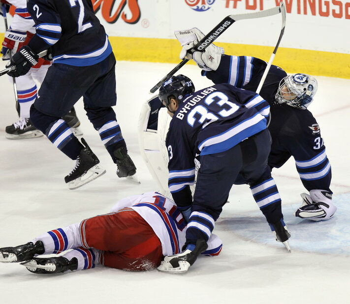 Winnipeg Jets Dustin Byfuglien puts down New York Rangers J.T. Miller hard in a collision with Ondrej Pavelec in the second period Tuesday. Byfuglien's crosscheck didn't get a penalty during the game, but it is expected to be reviewed by NHL officials.