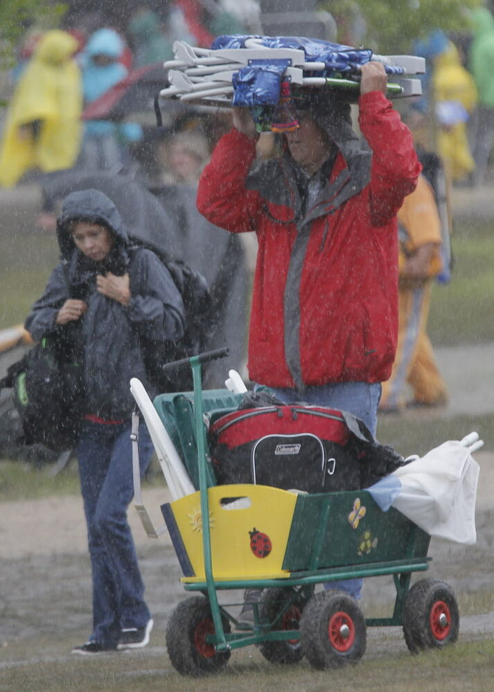 Fans took shelter from the rain anyway they could on the final day of Folk Fest Sunday, July 13, 2014.  (Winnipeg Free Press)