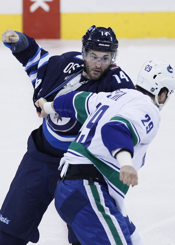 Winnipeg Jets' Anthony Peluso (14) and Vancouver Canucks' Tom Sestito (29) get in a scrap during the first period.  (John Woods / THE CANADIAN PRESS)