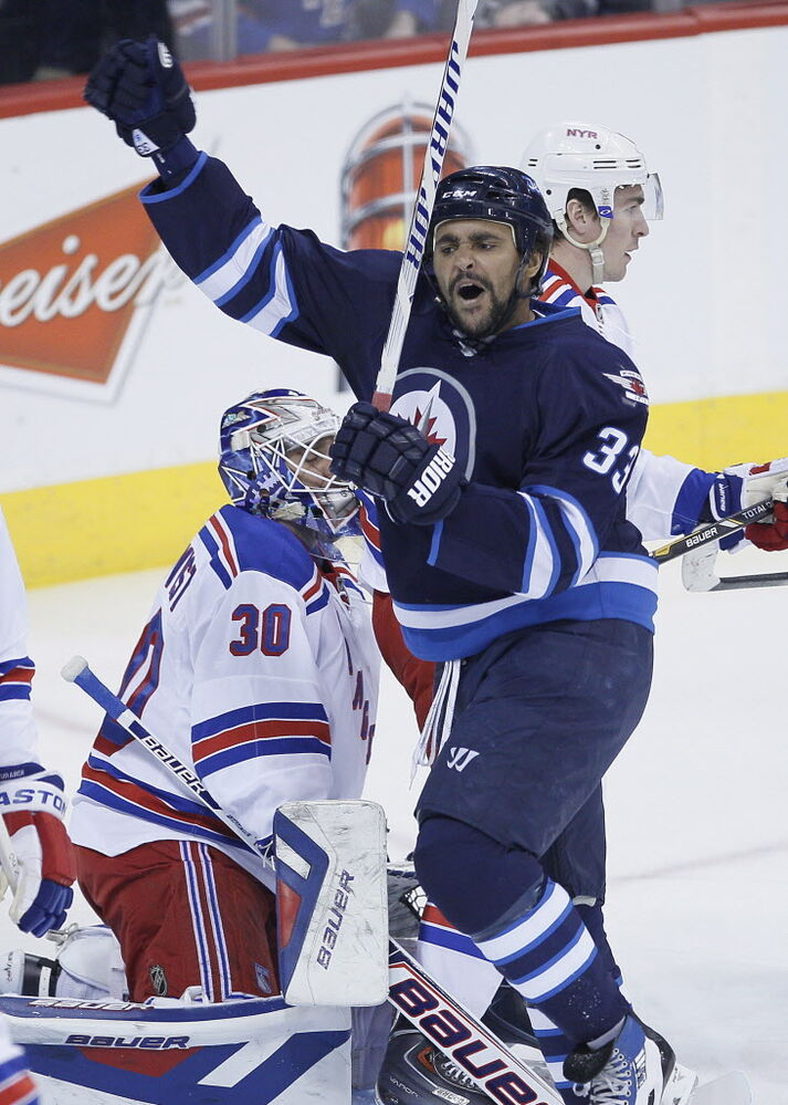 Winnipeg Jets' Dustin Byfuglien (33) celebrates his goal on New York Rangers goaltender Henrik Lundqvist (30) and Ryan McDonagh (27) during first period NHL action in Winnipeg.