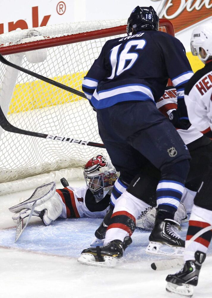Winnipeg Jets' Andrew Ladd (16) scores his second goal against New Jersey Devil New Jersey Devils goaltender Johan Hedberg (1) during third period action. (THE CANADIAN PRESS/John Woods)