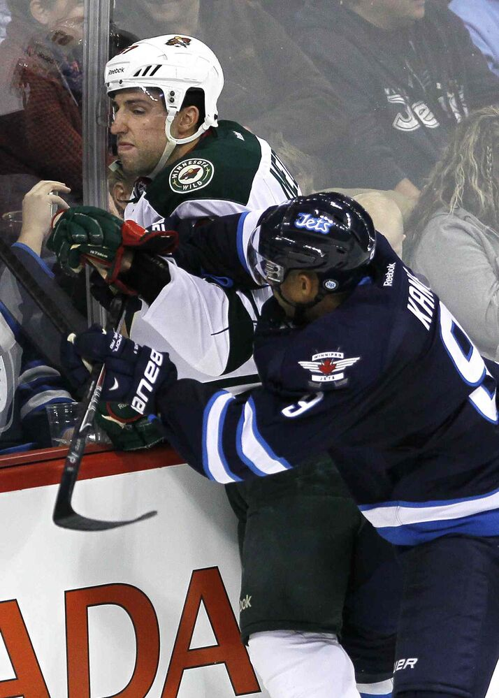 Winnipeg Jets' Evander Kane (9) takes out Minnesota Wild's Kyle Medvec (67) during the third period. (John Woods / The Canadian Press)