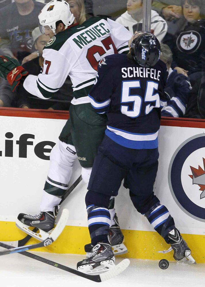 Minnesota Wild's Kyle Medvec (67) elbows Mark Scheifele along the boards during the third period.
