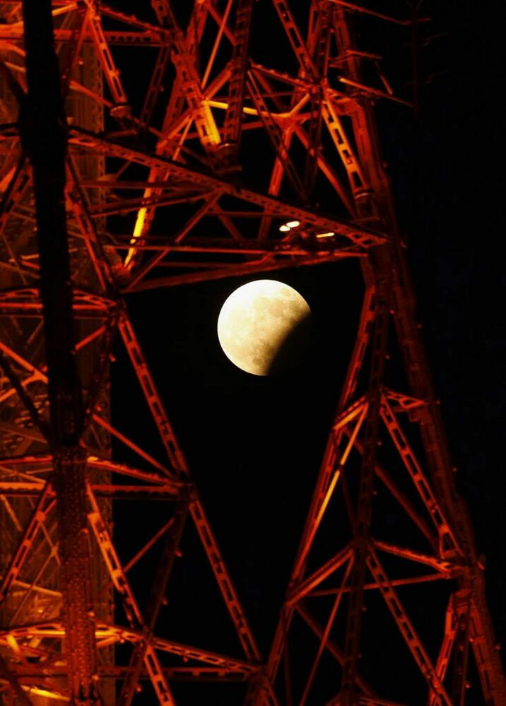 A partial lunar eclipse is seen through the Sapporo TV Tower in Sapporo, northern Japan. (AP Photo/Kyodo News)