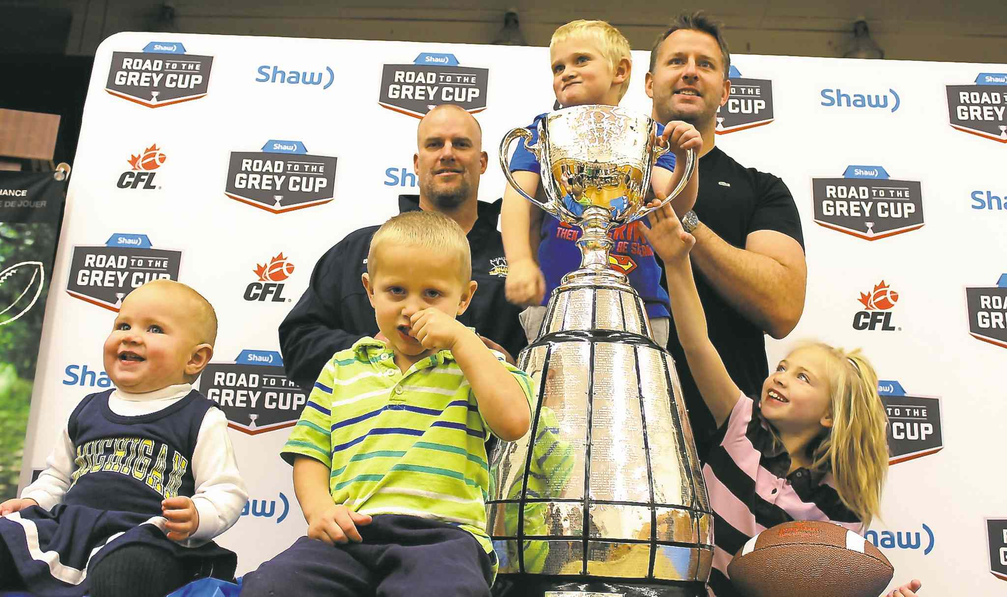 Snow Lake kids get a kick out of acquainting themselves with the Grey Cup Tuesday, under the supervision of former Bombers Brett MacNeil (left) and Doug Brown.