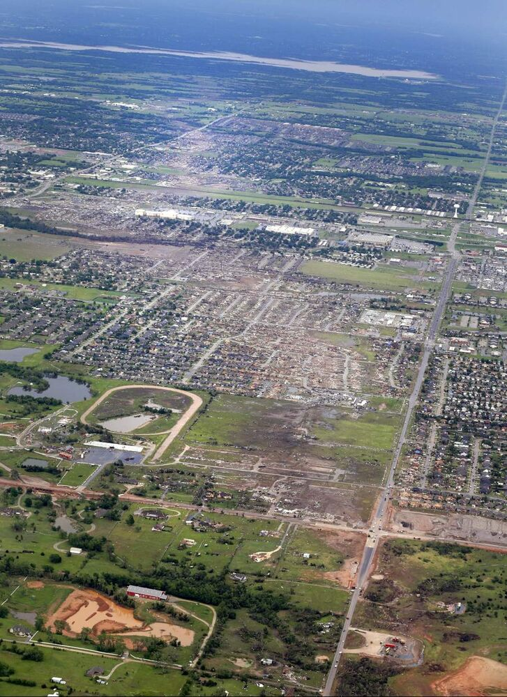 This Tuesday aerial photo shows, from bottom to top, the path Monday's tornado took through Moore, Okla. The huge tornado roared through the Oklahoma City suburb Monday, flattening entire neighborhoods and destroying an elementary school with a direct blow as children and teachers huddled against winds.  (CP)