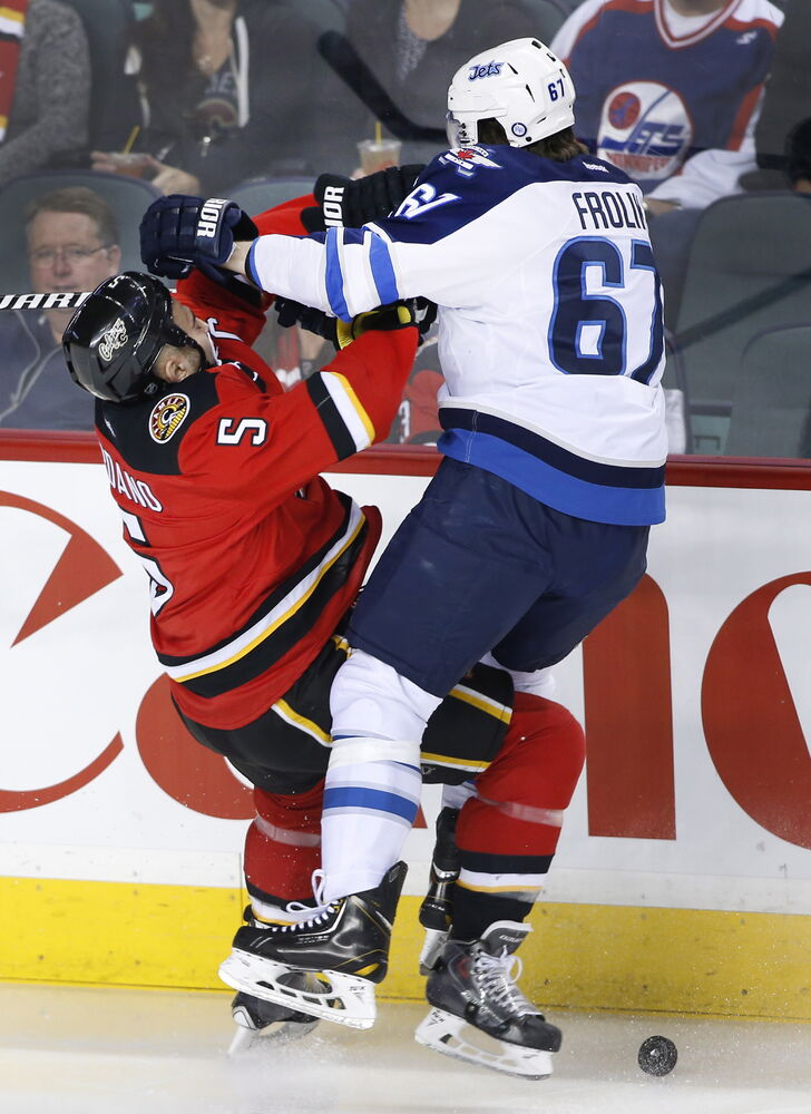 Winnipeg Jets' Michael Frolik, right, collides with Calgary Flames' Mark Giordano during the first period of Friday's NHL game in Calgary. (Larry MacDougal / The Canadian Press)