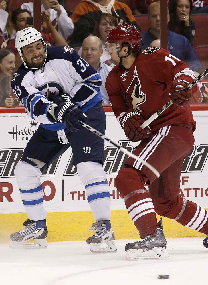 Winnipeg Jets' Dustin Byfuglien (33) passes the puck before being hit by Arizona Coyotes' Martin Hanzal (11), of the Czech Republic, during the first period of an NHL hockey game Thursday. (Ross D. Franklin / The Associated Press)