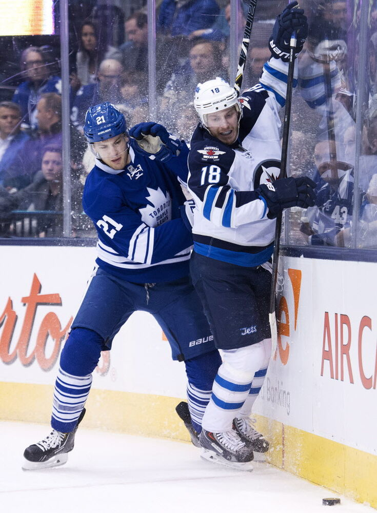Toronto Maple Leafs forward James van Riemsdyk (21) battles for the puck against Winnipeg Jets forward Bryan Little (18).