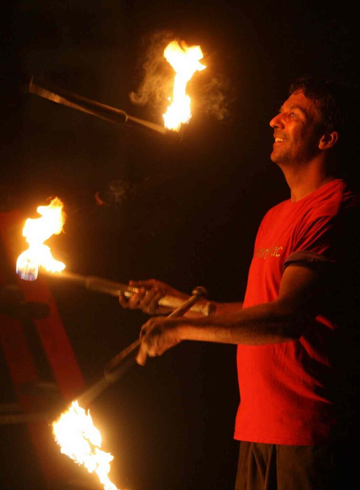 A festival sideshow entertainer juggles fire late Friday night.