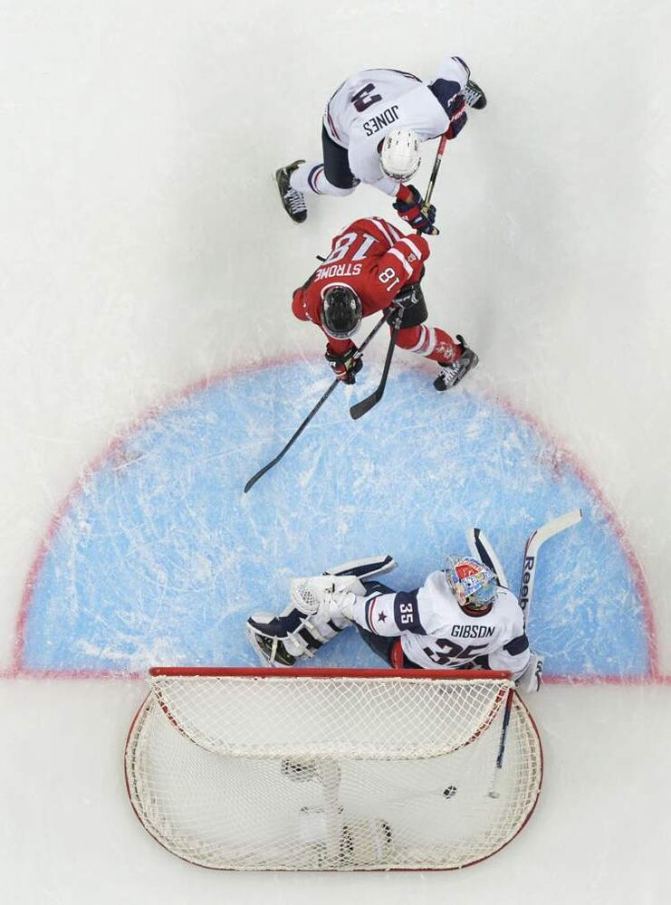 Team Canada forward Ryan Strome scores past Team USA goalie John Gibson as USA defenceman Seth Jones looks on Sunday.