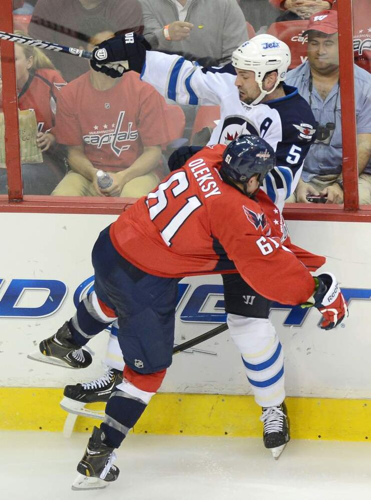 Washington Capitals' Steven Oleksy (61) and Winnipeg Jets defenceman Mark Stuart crash along the boards during the third period.