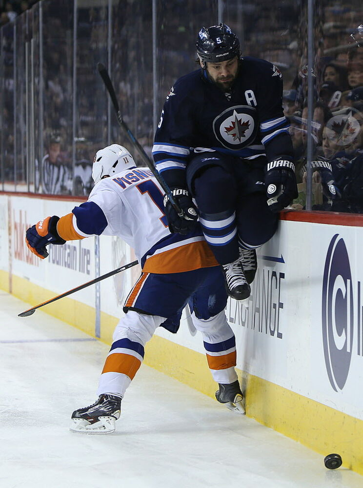 Winnipeg Jets defenceman Mark Stuart dodges a check from New York Islanders defenceman Lubomir Visnovsky during third-period NHL action at the MTS Centre. (Jason Halstead / Winnipeg Free Press)